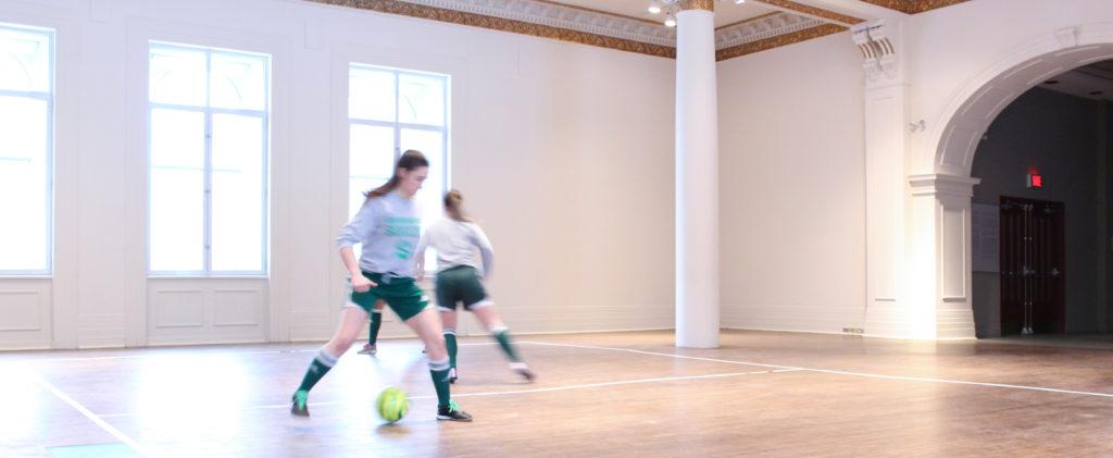 Deux membres féminins d'une équipe sportive jouent au soccer dans le Musée des beaux-arts de Sherbrooke